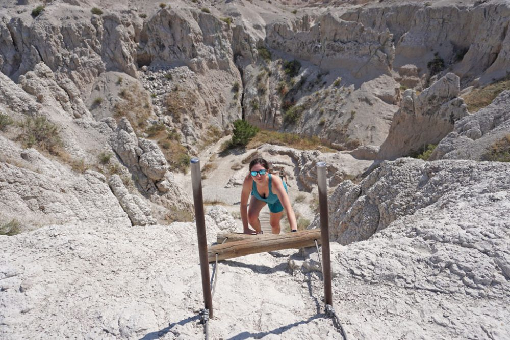 White woman in a teal tank top looking up at the camera as she descends a wooden ladder into a canyon