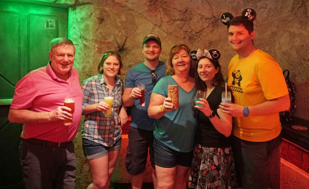 Group holding drinks inside Oga's Cantina