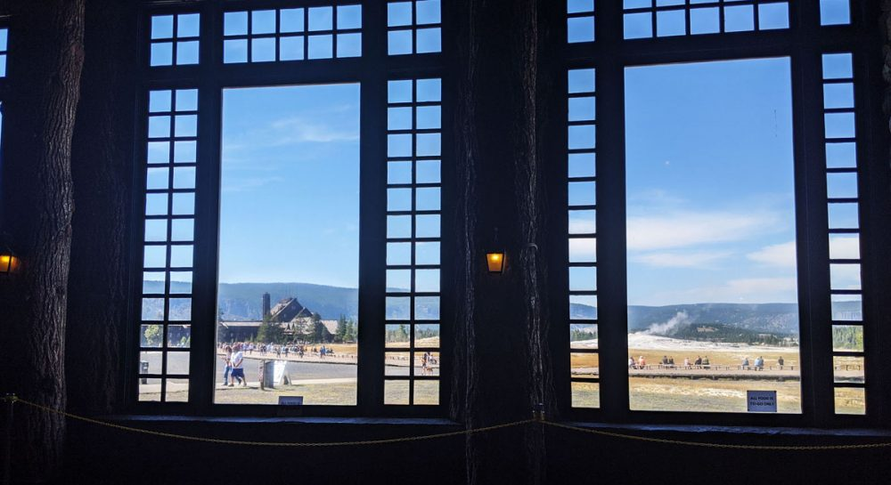 Wooden beams covered with bark in front of large windows overlooking Old Faithful and a large wooden hotel structure
