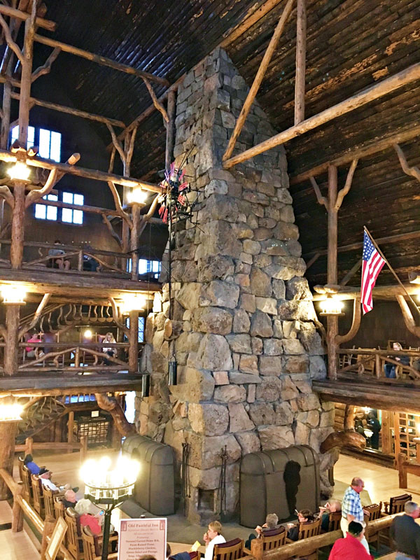 Tall stone fireplace surrounded by soaring wooden beams inside the Old Faithful Lodge in Yellowstone