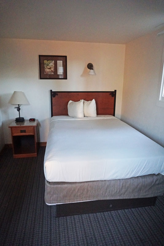 Bed with white sheets and a small nightstand next to it in the Old Faithful Lodge Cabins