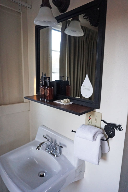 White sink under a small mirror with an overhead light and a towel on a bar next to it