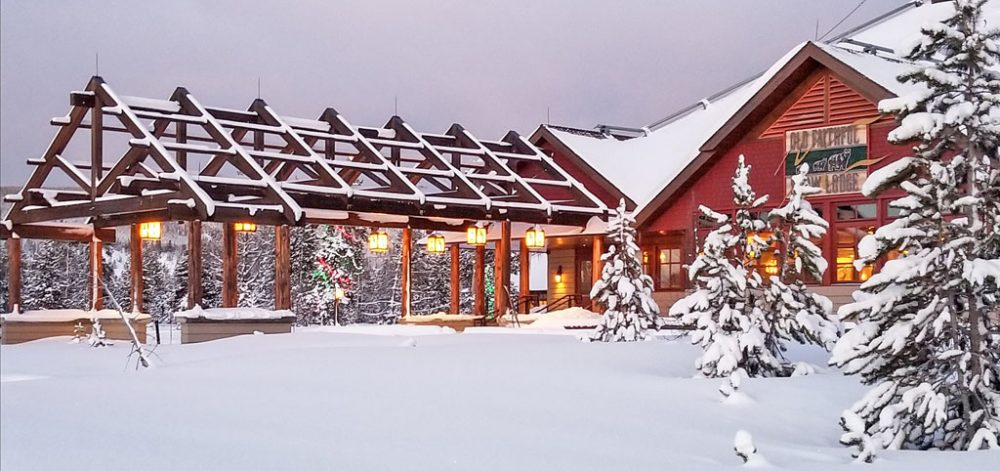 Wooden lodge with a large portico covered with snow under grey winter skies