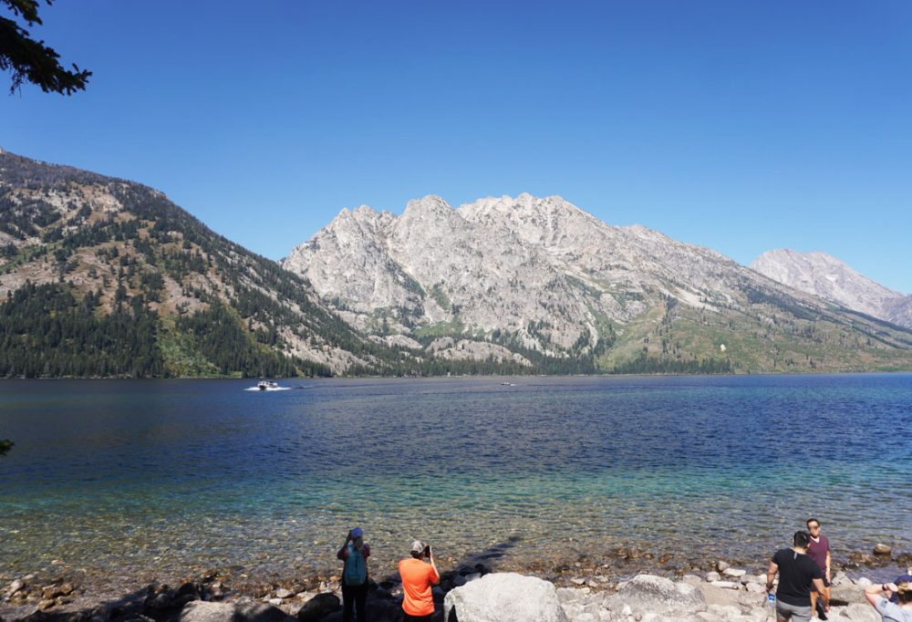 Visitors taking photographs on the shores of a large alpine lake with the Grand Teton mountains in the background