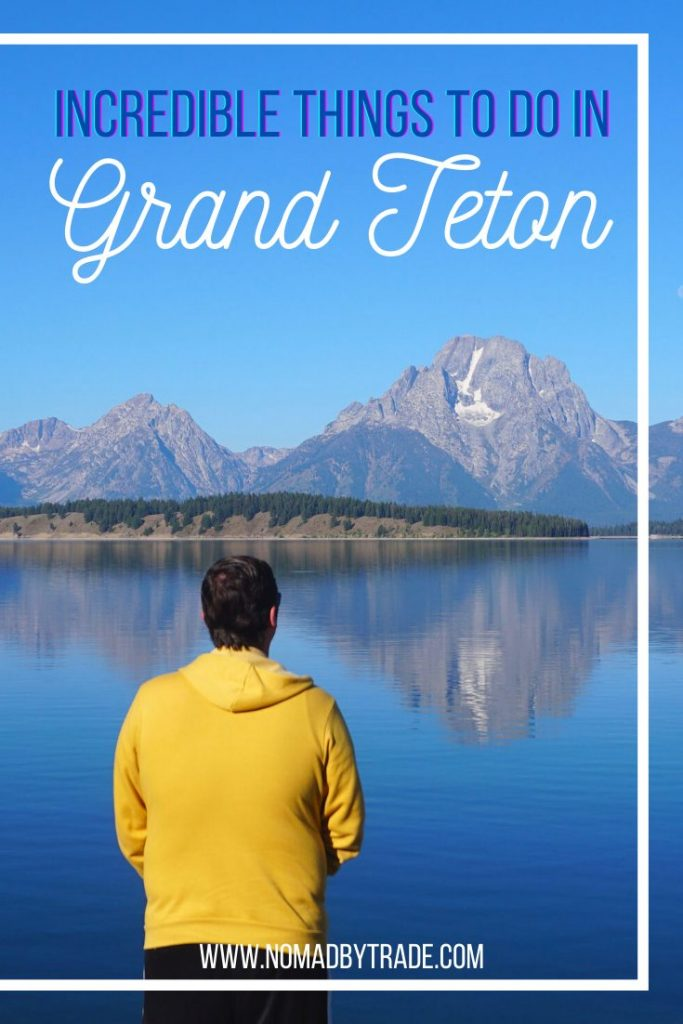 """Man in a yellow hoodie with his back to the camera looking out at the reflection of mountain peaks in calm lake waters with text overlay reading """"incredible things to do in Grand Teton"""""""