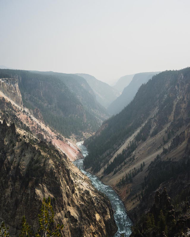 Photo of a river flowing through Yellowstone Canyon with hazy skies overhead