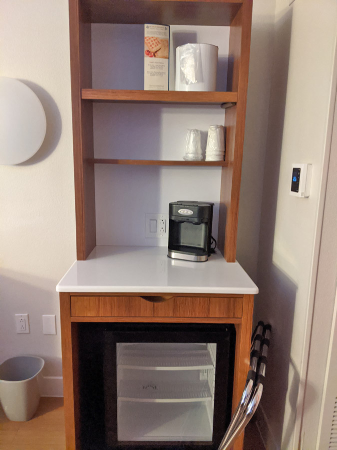 Pop Century room amenities, including refrigerator, coffee maker, cups, and tea