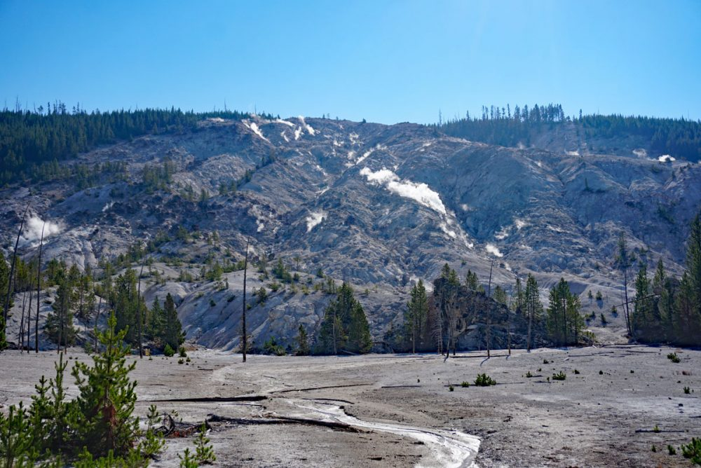Mountainside with steam pouring out of it in Yellowstone National Park