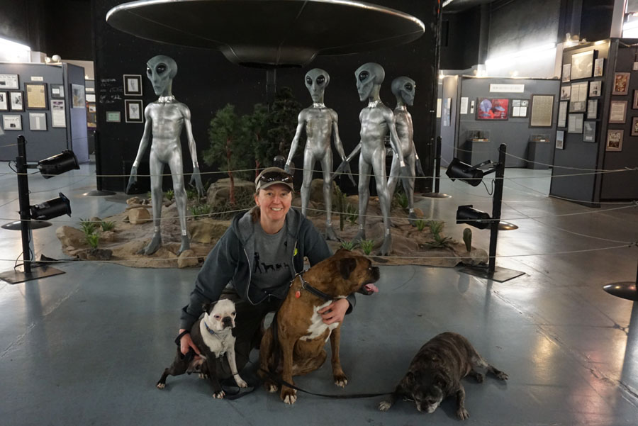 Woman posing with 3 dogs in front of alien statues in Roswell, New Mexico