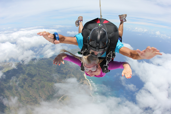 Woman and man skydiving together over Oahu