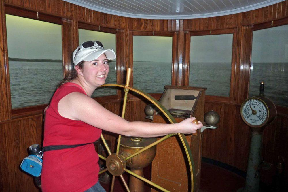 Woman posing with a ship wheel in the Coast Guard museum
