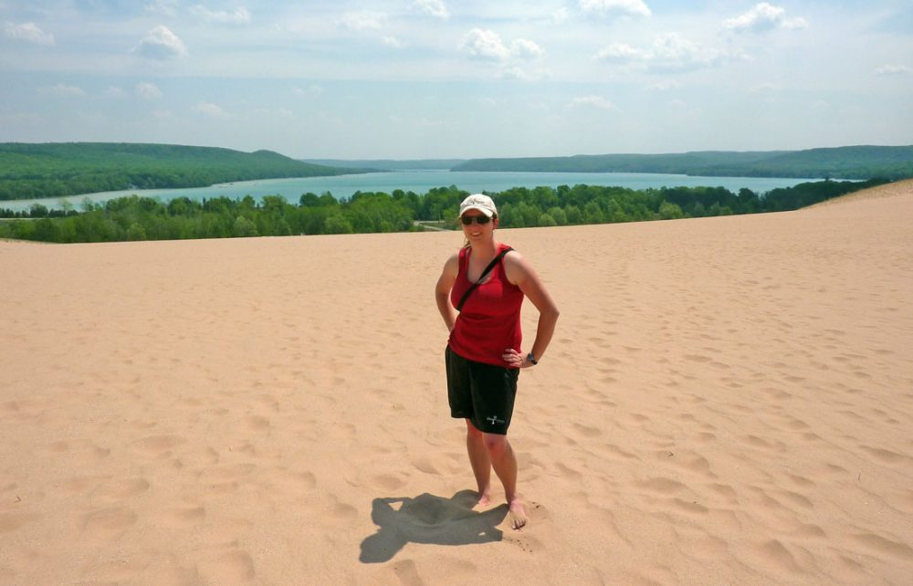 Woman atop the Dune Climb at Sleeping Bear Dunes National Lakeshore with Glen Lake in the distance