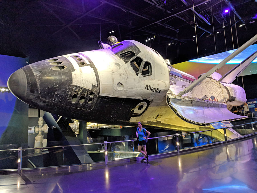Woman posing in front of the space shuttle Atlantis