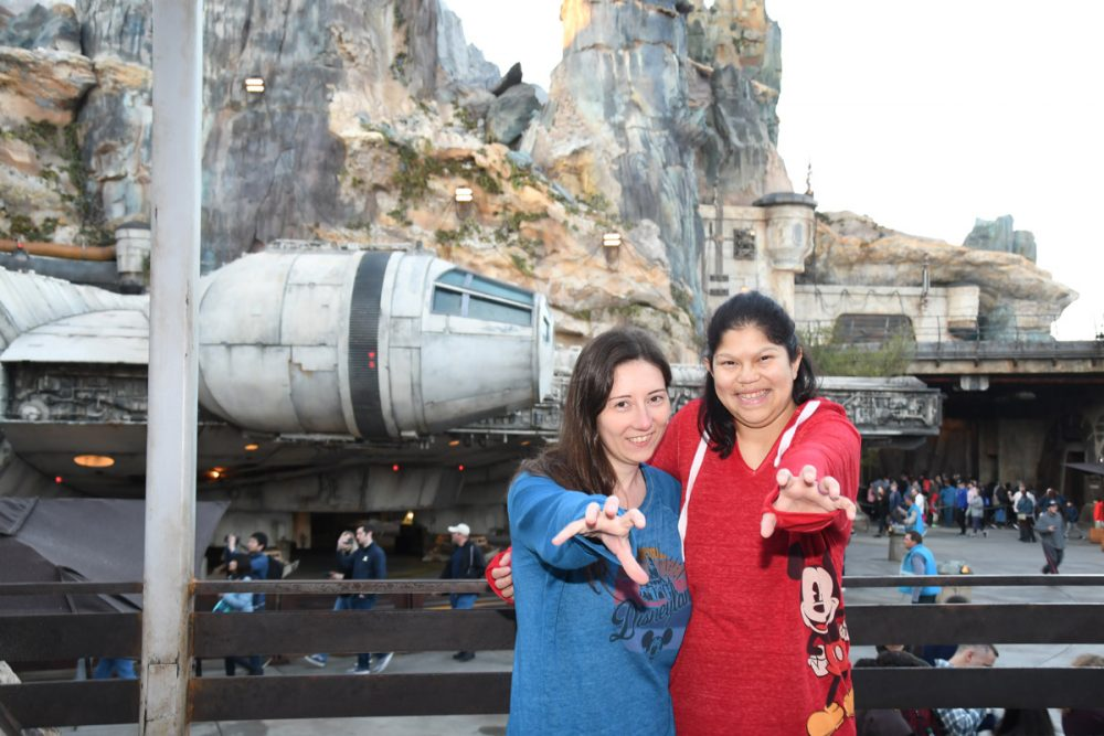 Two women pretending to use The Force in front of the Millennium Falcon