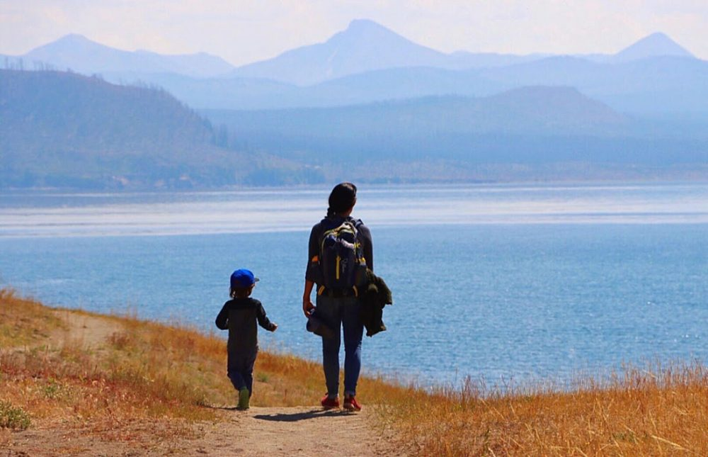 A hiker with a young child silhouetted against the hazy blue of a large mountain lake as they walk along a grassy path on the Storm Point Trail