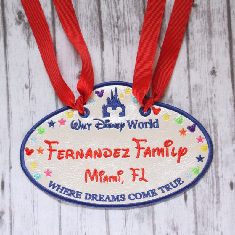 """Nametag shaped like a Cast Member tag with ribbons with text reading """"Fernandez Family Miami, FL"""""""