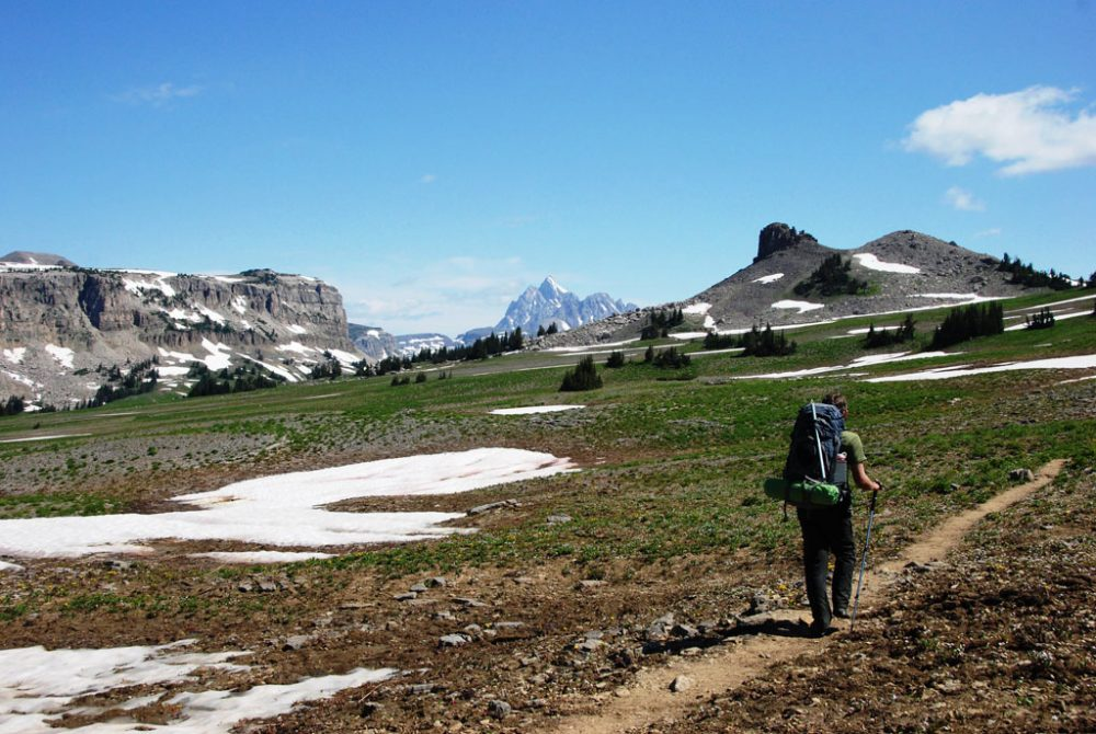 Photo of a hiker on the Teton Crest Trail, one of the most challenging Grand Teton hikes, passing through an open field with mountain peaks in the distance