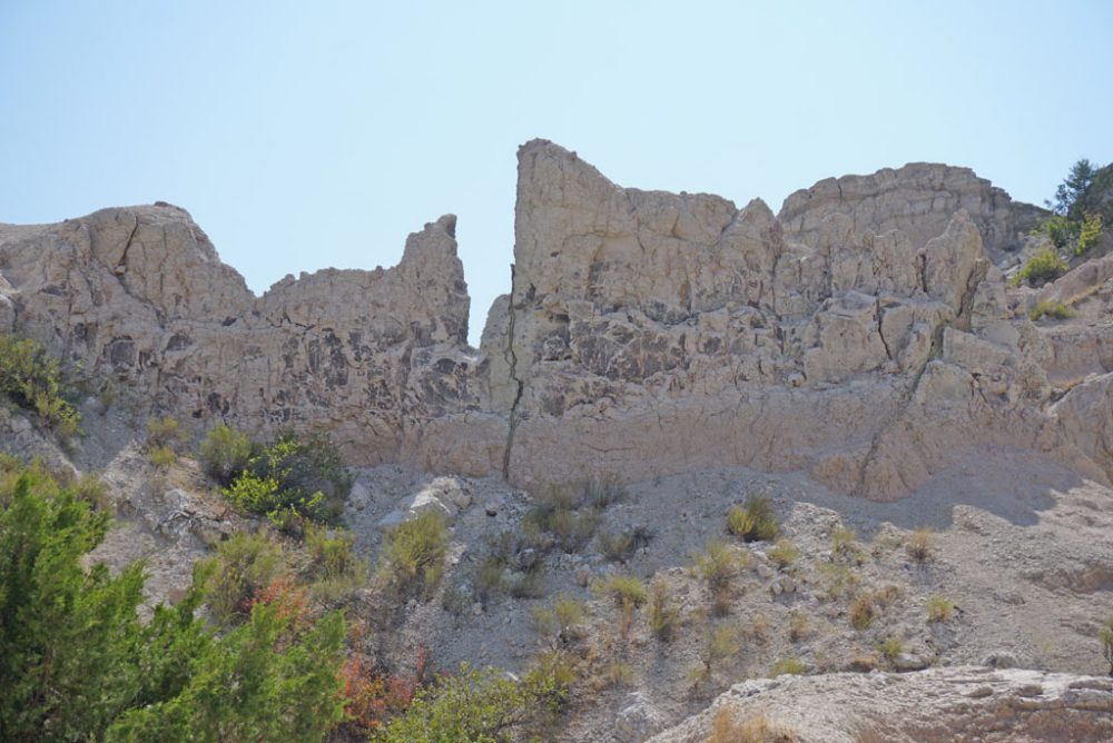 Chalky white canyon walls under blue skies at the start of the Notch Trail in Badlands National Park