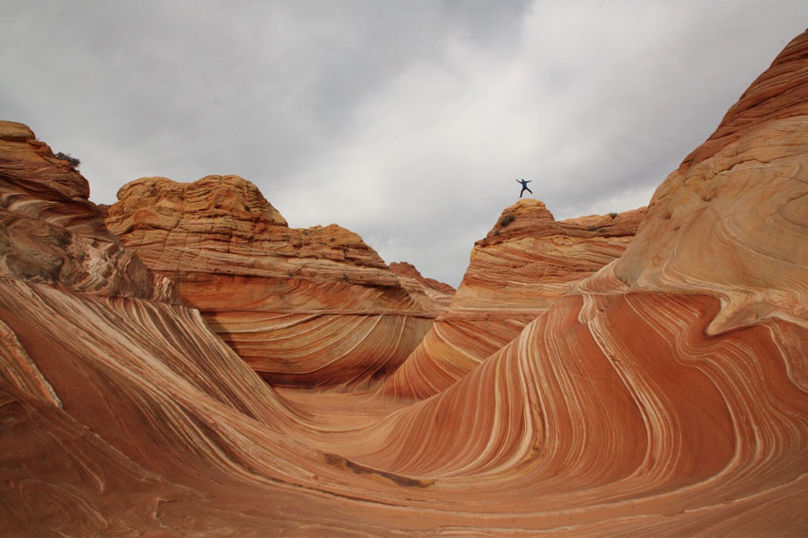 Hiker jumping above The Wave in Arizona