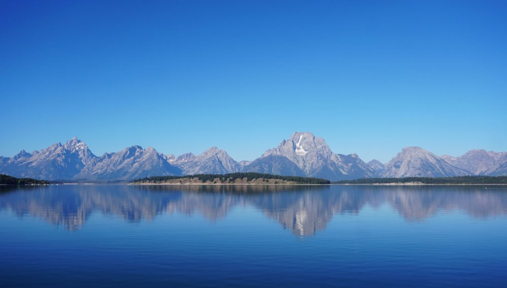 Towering mountains in Grand Teton National Park reflected on calm waters of a large lake under a clear blue sky