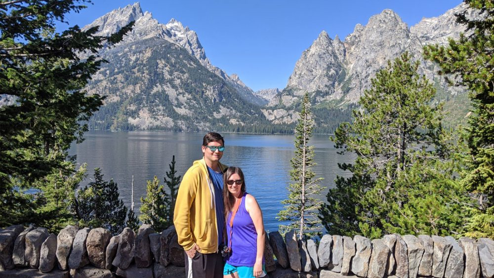 White man and white woman in summer clothes posing in front of a small lake with mountain peaks in the background