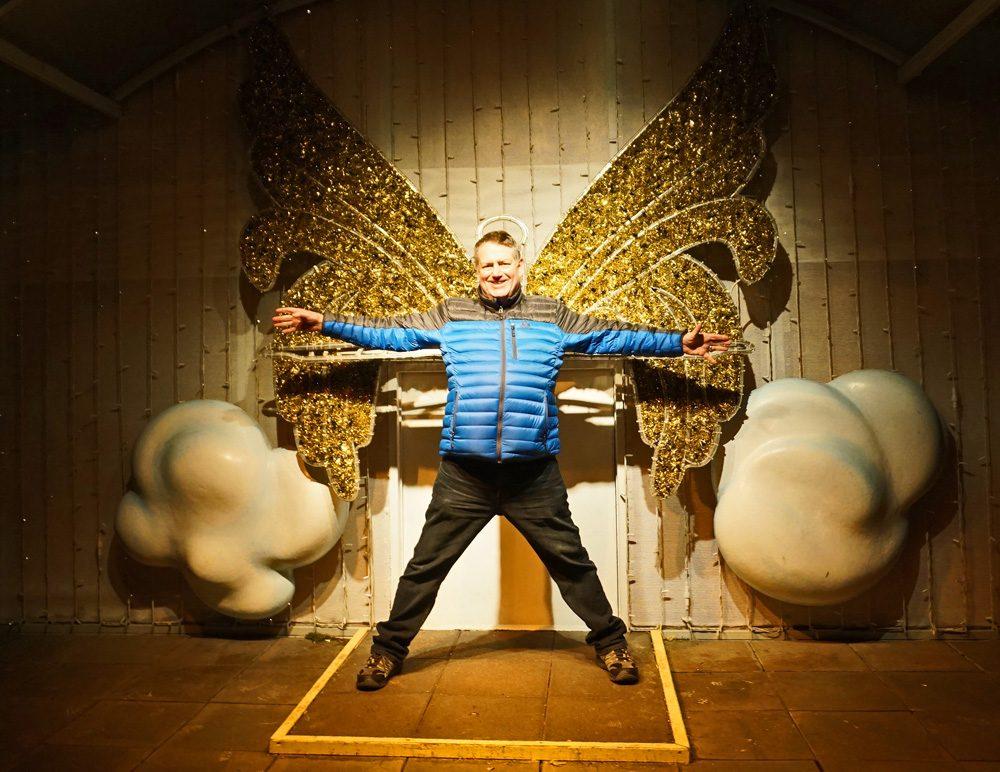 Man posing in front of an angel wings Instagram wall