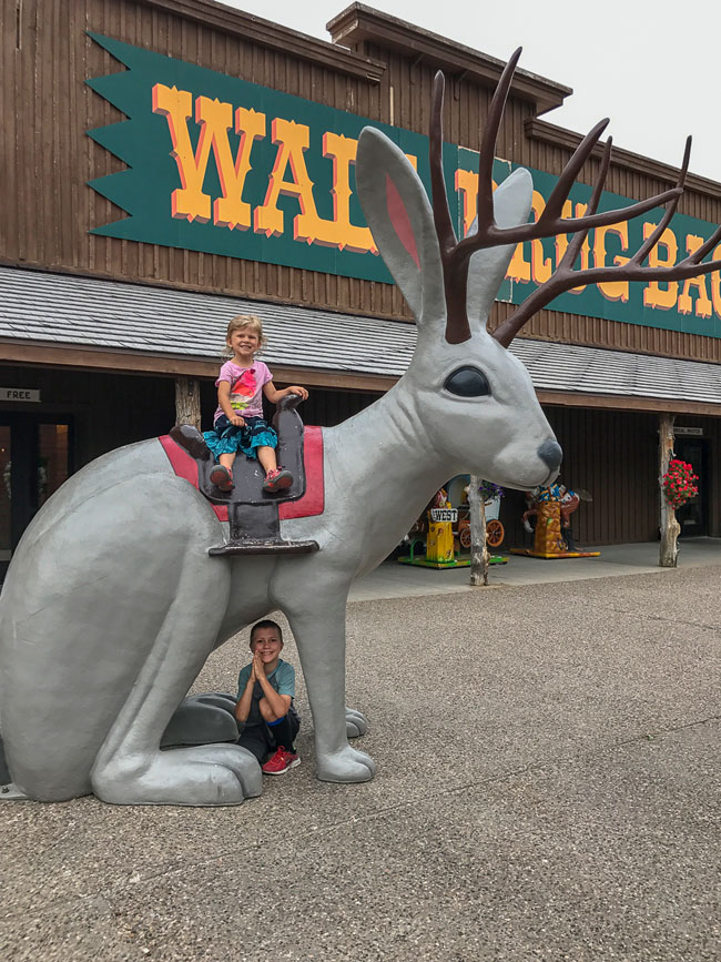 Children posing atop a giant statue of a jackalope at Wall Drug in South Dakota