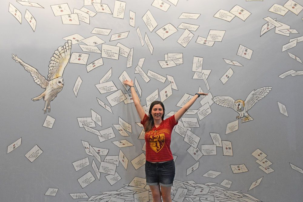 Woman standing in front of a wall of Hogwarts letters