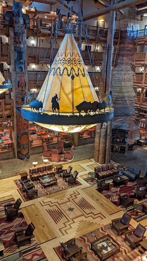 High ceilinged lobby of Disney's Wilderness Lodge with seating, wooden beams, a fireplace, and teepee chandeliers