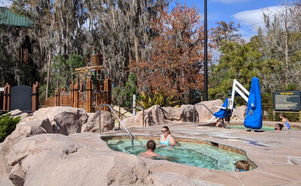 Swimmers relaxing in outdoor hot tubs with a handicap lift in the background