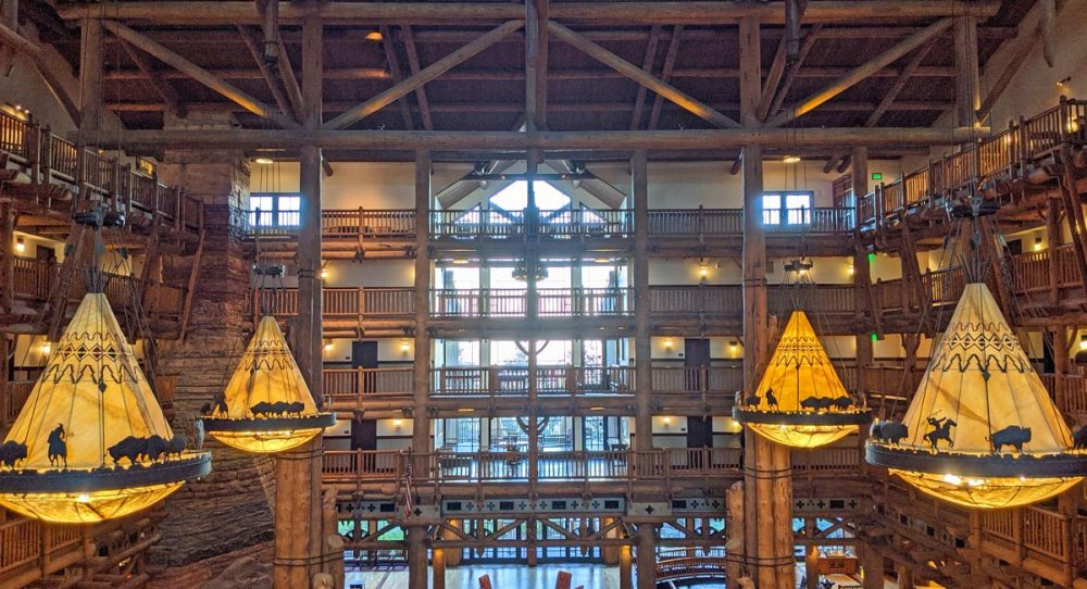 Teepee-shaped chandeliers hanging from dark wooden beams in the lobby of Disney's Wilderness Lodge