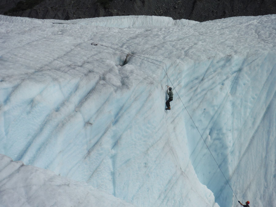 Person climbing pale blue glacial ice in Wrangell St. Elias National Park