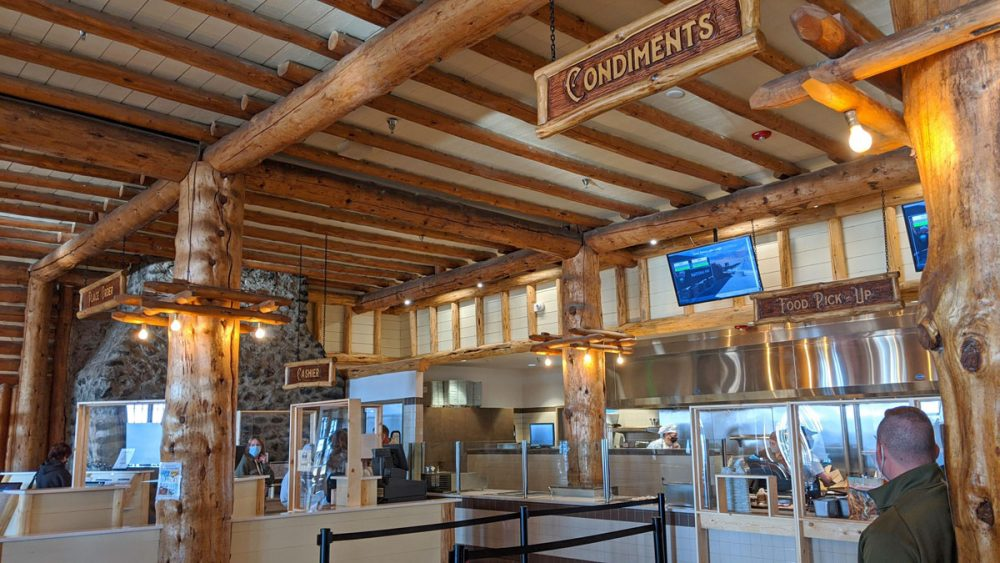 Wooden beamed room with food service counters and a sign for Condiments