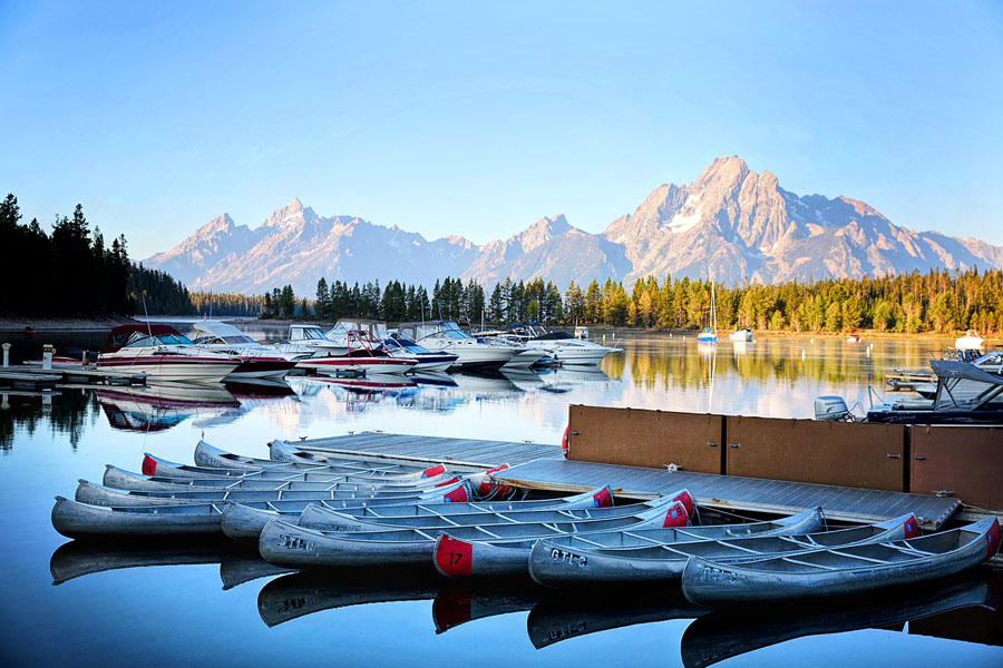 Boats on a lake in front of mountains in Grand Teton National Park